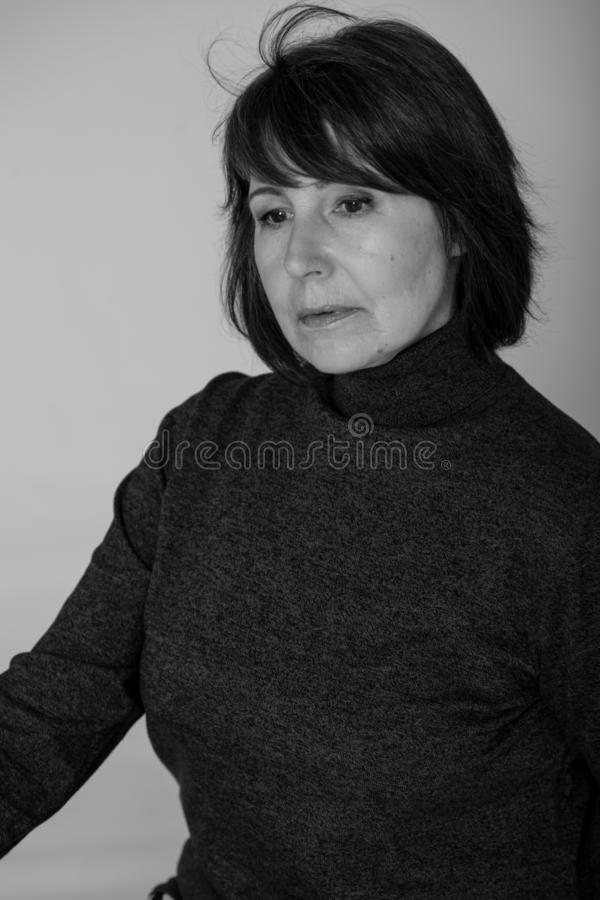Strange mood. Close-up monochrome portrait old woman thoughtful look. Strange mood. Close-up black and white portrait of a woman without retouching sitting on a royalty free stock image