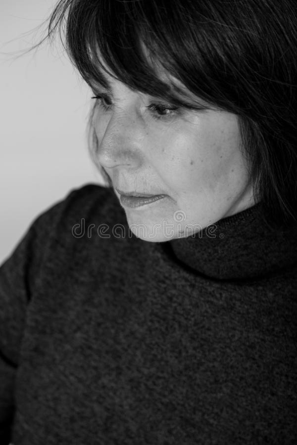 Strange mood. Close-up monochrome portrait old woman thoughtful look. Strange mood. Close-up black and white portrait of a woman without retouching sitting on a stock image