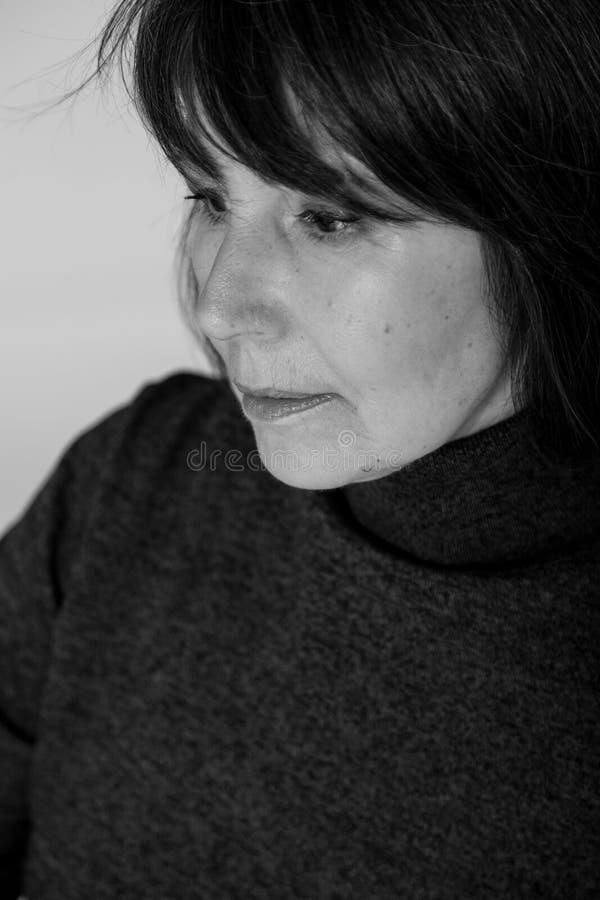 Strange mood. Close-up monochrome portrait old woman thoughtful look stock image