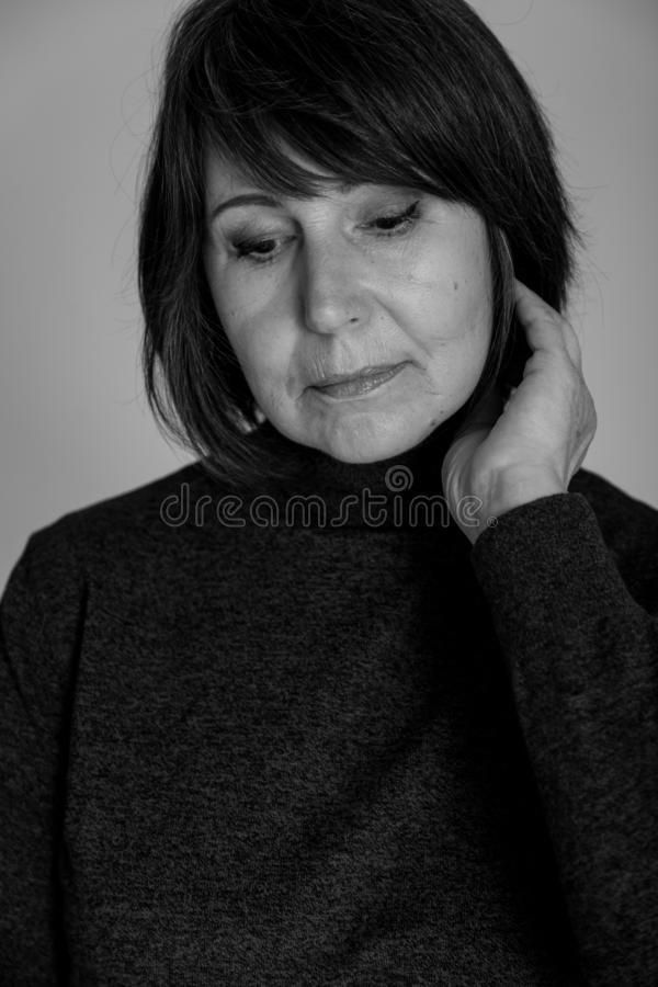 Strange mood. Close-up monochrome portrait old woman thoughtful look. Strange mood. Close-up black and white portrait of a woman without retouching sitting on a stock photo