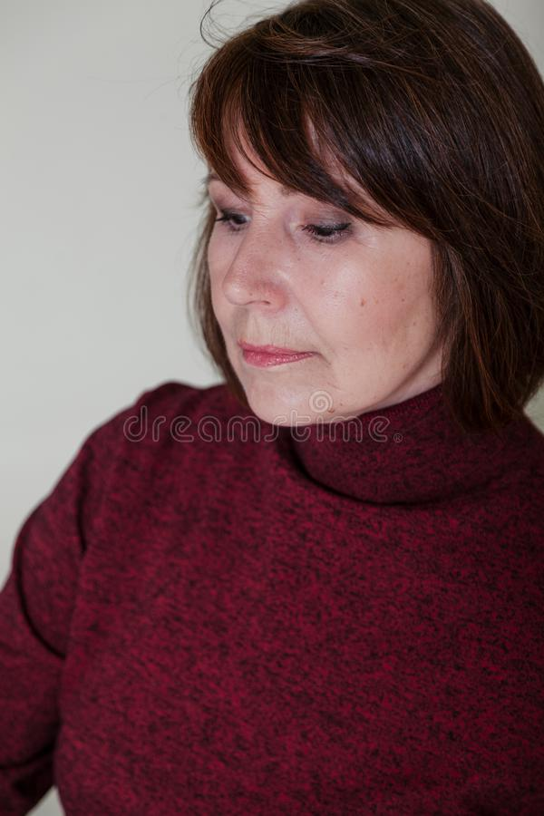 Strange mood. Close-up portrait old woman with thoughtful look. Strange look. Close-up portrait of a woman without retouching sitting on a bright monophonic royalty free stock photography