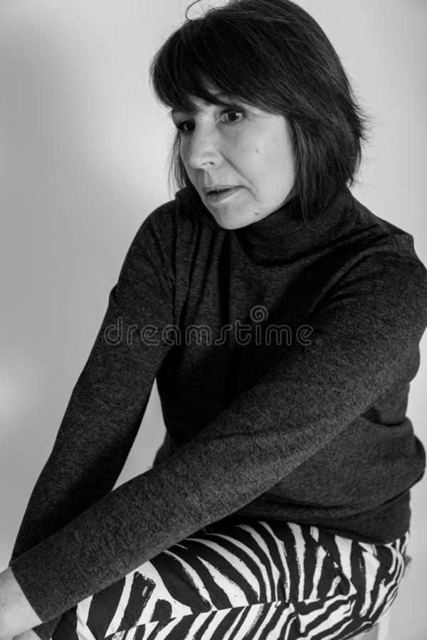 Strange mood. Monochrome portrait of old woman with thoughtful look. Strange mood. Black and white portrait of a woman without retouching sitting on a bright royalty free stock image