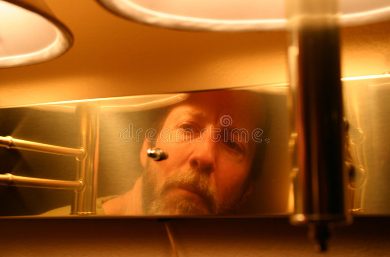 Strange Reflections 1. A middle-aged man with mustache and beard takes a look at his reflection through a brass light fixture which hangs on a wall. The light royalty free stock image