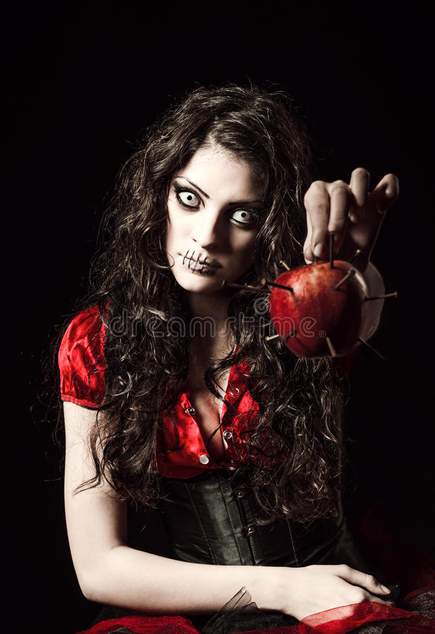 Strange scary girl with mouth sewn shut holds apple studded with nails stock photography