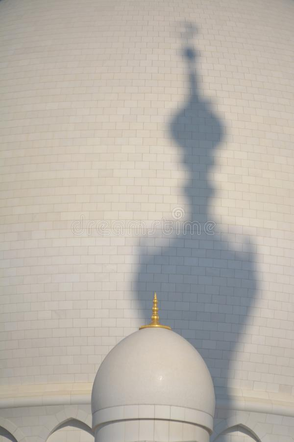 Strange shadow of a mosque tower. On a white dome stock photo