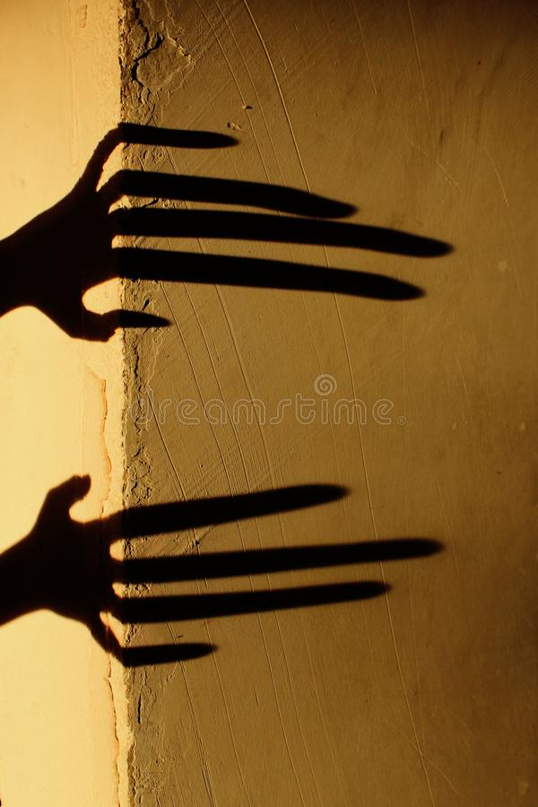 Strange Shadow On The Wall.Terrible Shadow. Abstract Background. Black Shadow Of A Big Hand On The Wall. Silhouette Of A Hand On T royalty free stock image