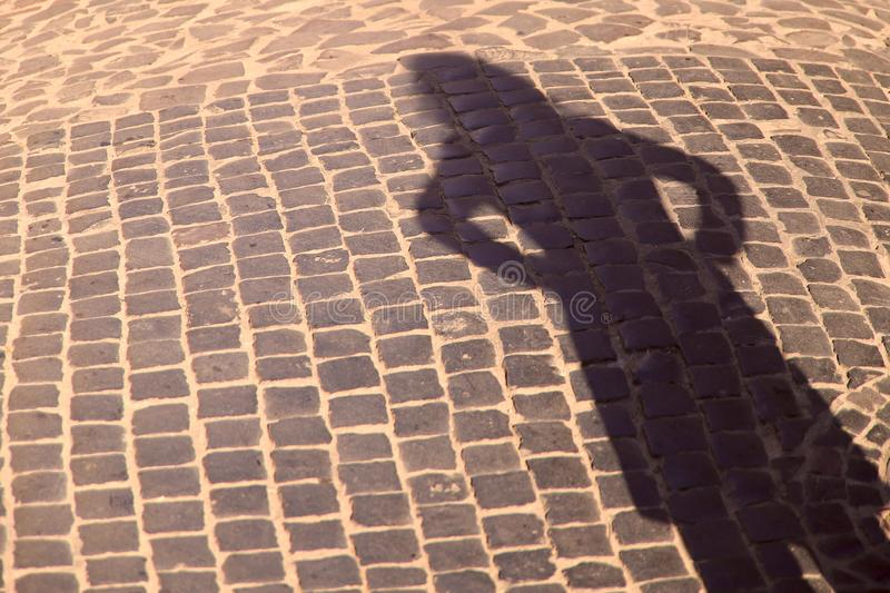Strange shadow of a woman`s silhouette on an old stone road. Black shadow, female hand. stock photos