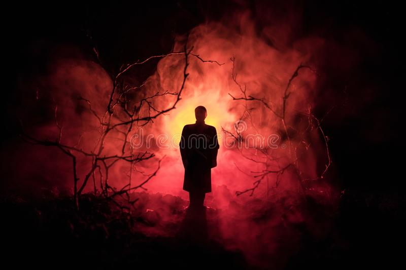 strange silhouette in a dark spooky forest at night, mystical landscape surreal lights with creepy man. Toned royalty free stock photos