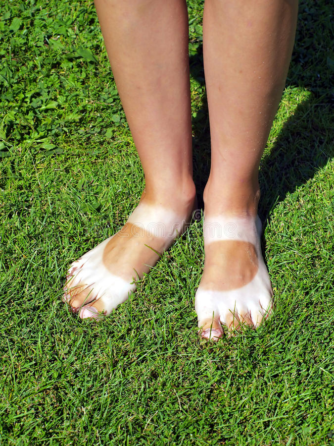 Strangely Tanned Legs On The Lawn Stock Photography