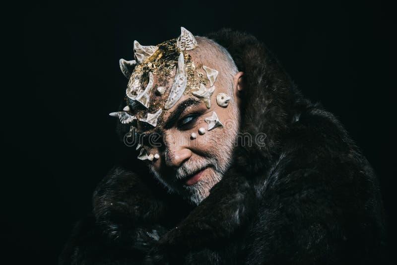 Straniero, demone, trucco del mago Concetto di fantasia e di orrore Uomo con le spine o le verruche in pelliccia Demone sul nero immagini stock