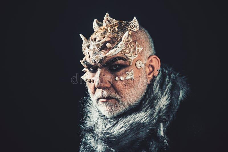 Straniero, demone, trucco del mago L'uomo senior con la barba bianca si ? vestito come il mostro Demone su fondo nero, spazio del immagini stock libere da diritti