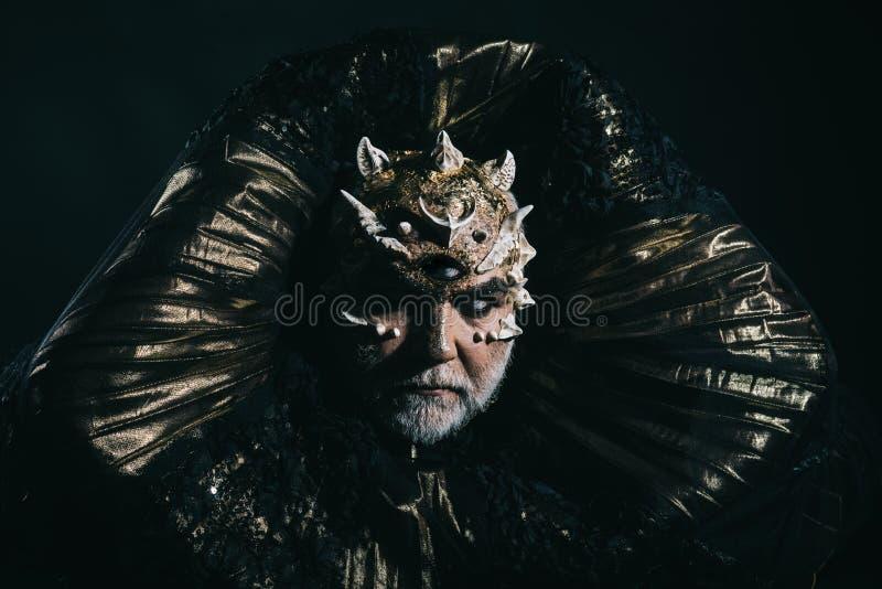 Straniero, demone, trucco del mago Uomo con il terzo occhio, le spine o le verruche Demone con il collare dorato su fondo nero or fotografia stock libera da diritti