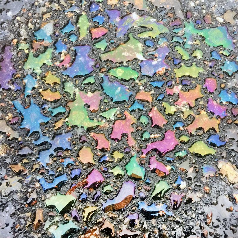 Straripamenti iridescenti dei punti della benzina sulla superficie dell'acqua sull'asfalto fotografia stock