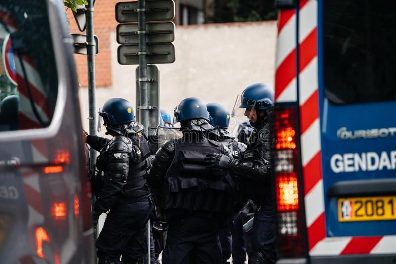 Rear view of French police officers gendarmes at yellow vests protest. Strasbourg, France - Apr 28, 2019: Male officers rear view gendarmes near police vans stock photography