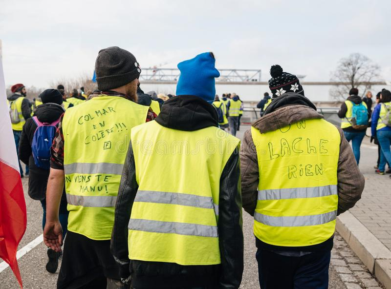 Rear view of riends vearing green yellow vests at protest. STRASBOURG, FRANCE - FEB 02, 2018: Friends demonstrating during protest of Gilets Jaunes Yellow Vest royalty free stock photography