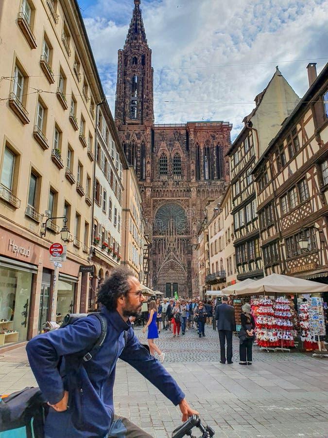 STRASBOURG, FRANCE - juin 2019 : Vue sur Strasbourg Cathedral Cathedrale de Notre-Dame et un homme passant par sur la bicyclette images libres de droits