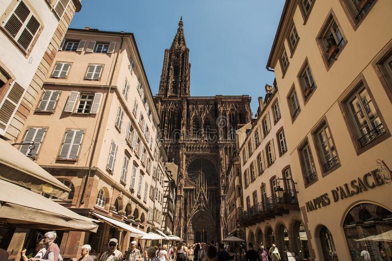 STRASBOURG, FRANCE - JULY 05, 2019: Notre Dame de Strasbourg. Strasbourg street with tourists. Gothic church. Catholic cathedral stock photography