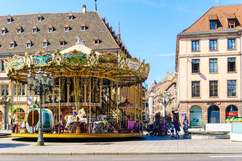 STRASBOURG, FRANCE - JULY 18, 2017: Old vintage carousel merry-go-round in the PLace Kleber, Strasbourg with people admiring the m. Ajestic attraction and the royalty free stock image