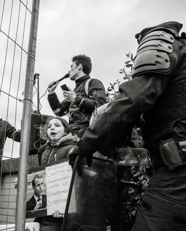 Global movement Fridays for Future police protesters placards government. STRASBOURG, FRANCE - MAR 15, 2019: Young french girl with placard portrait of Emmanuel royalty free stock photo