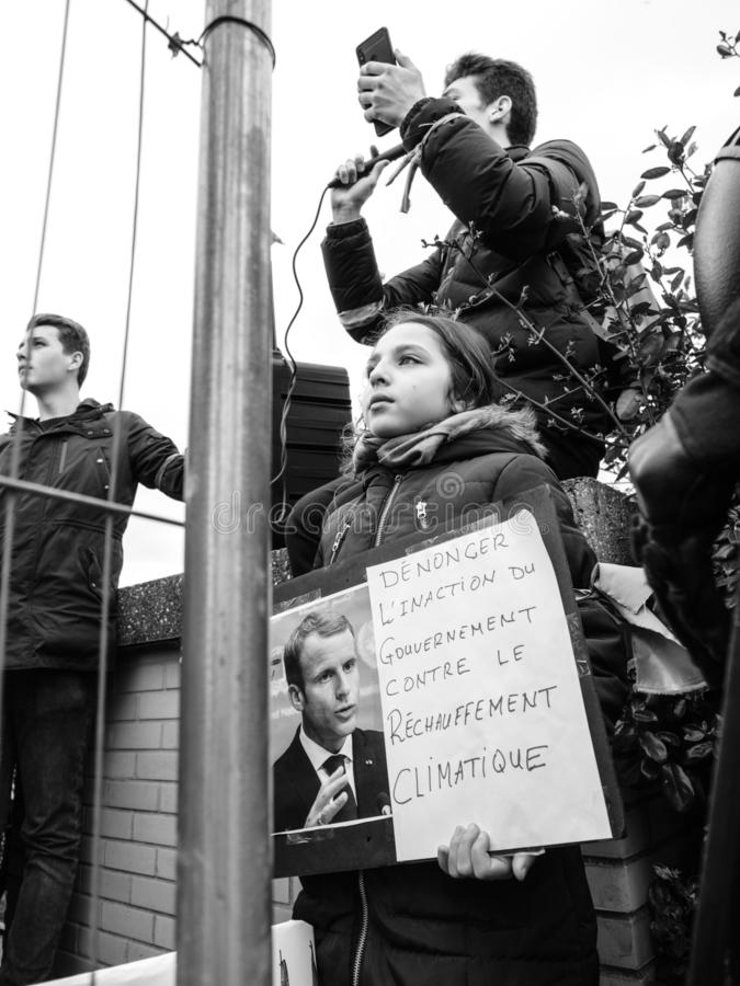 Global movement Fridays for Future police protesters placards government. STRASBOURG, FRANCE - MAR 15, 2019: Young french girl with placard portrait of Emmanuel royalty free stock image