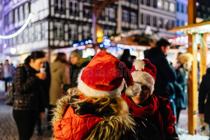 Two adult women wearing funny Christmas Hats. STRASBOURG, FRANCE - NOV 29, 2017: Evening city scene with two women wearing red santa hats talking in center of stock images