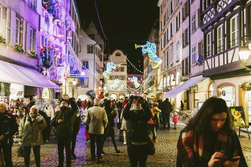 Woman using smartphone at Strasbourg Christmas Market at dusk royalty free stock photos