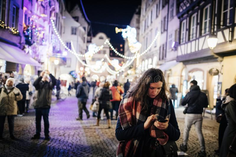 Woman using smartphone at Strasbourg Christmas Market at dusk stock photography