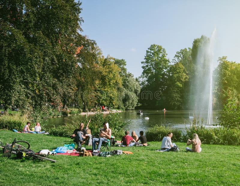 Orangerie park in Strasbourg with people near lake. STRASBOURG, FRANCE - SEP 24, 2017: Crowd of people enjoying the sun on an early autumn day in Strasbourg royalty free illustration