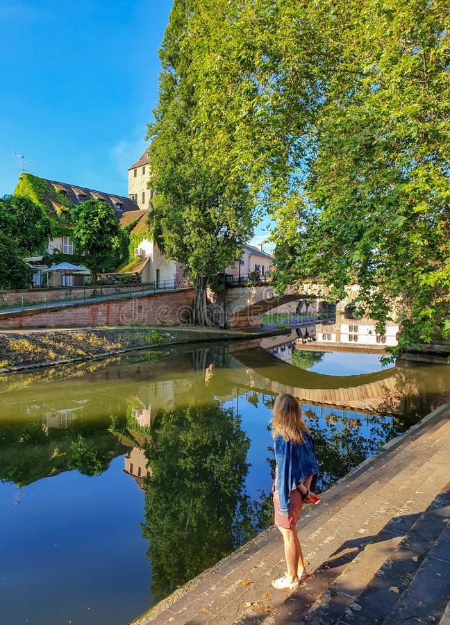 STRASBOURG FRANKRIKE - Juni 2019: ett flickaanseende på flodbanken, nära den pittoreska kanalen av Petite France arkivfoto