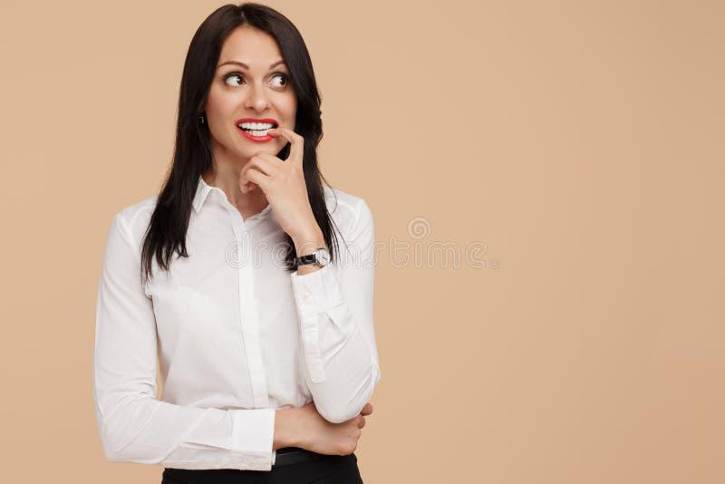 Strasząca młoda nowożytna biznesowa kobieta nad beżowym tłem zdjęcie royalty free
