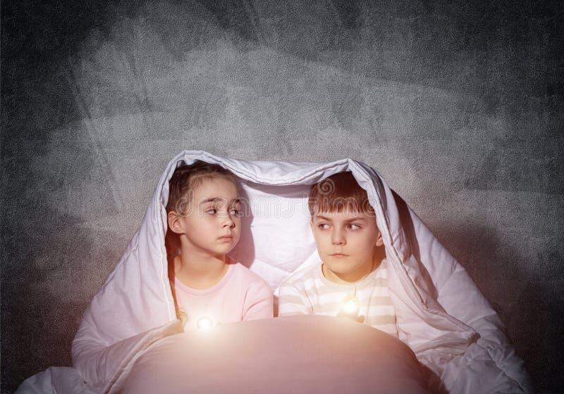 Straszący dzieci z latarkami w łóżku fotografia stock
