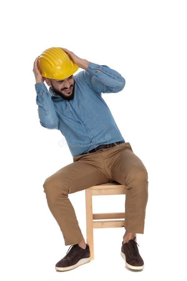 Straszący mężczyzny obsiadanie z rękami na żółtym hełmie fotografia stock