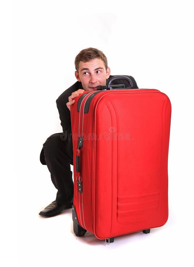 Straszna biznesowego mężczyzna kryjówka za czerwonym bagażem zdjęcie stock