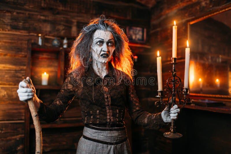 Straszna czarownica z candlestick i trzciną czyta czary zdjęcia stock