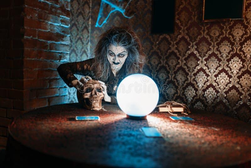 Straszna czarownica z ludzką czaszką nad kryształową kulą zdjęcie royalty free