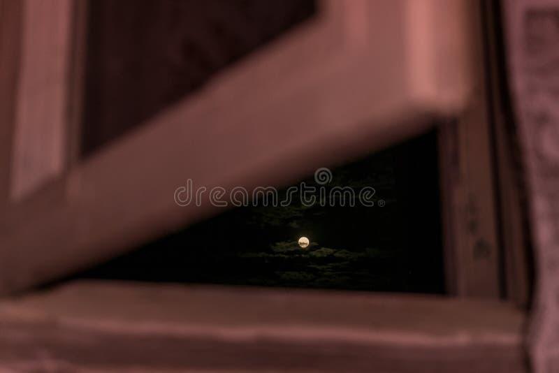 Straszna księżyc między chmurami od okno obraz royalty free