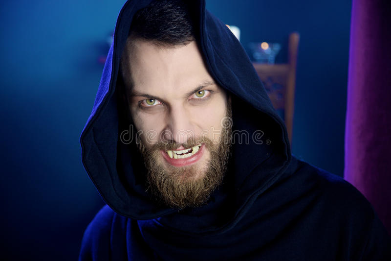 Strasznego męskiego wampira przyglądająca kamera z fangs zdjęcie stock