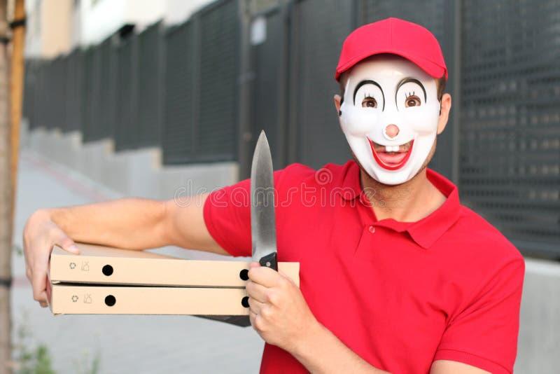 Strasznej pizzy doręczeniowy facet z nożem zdjęcie stock