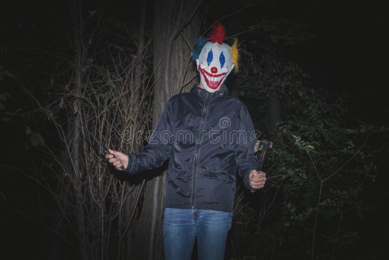 Straszny błazen w drewnie z nożem i ax zdjęcie stock