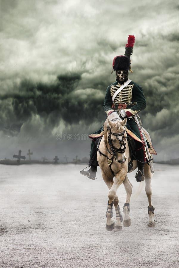 Straszny zredukowany Napoleon oficer jedzie białego konia z grób krzyżuje za on w tle z zmrokiem i i obrazy stock