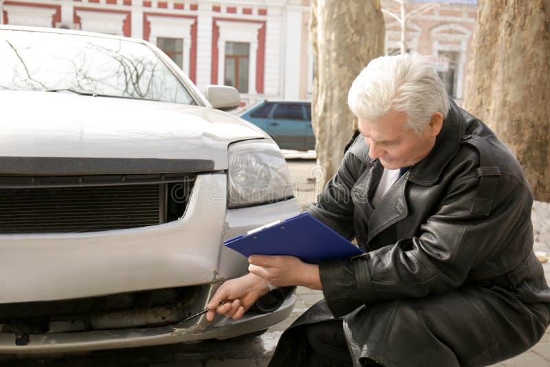 Strata nastawiacz sprawdza samochód po wypadku obraz stock