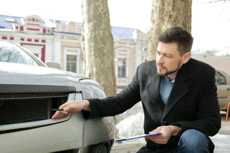 Strata nastawiacz sprawdza samochód po wypadku fotografia stock