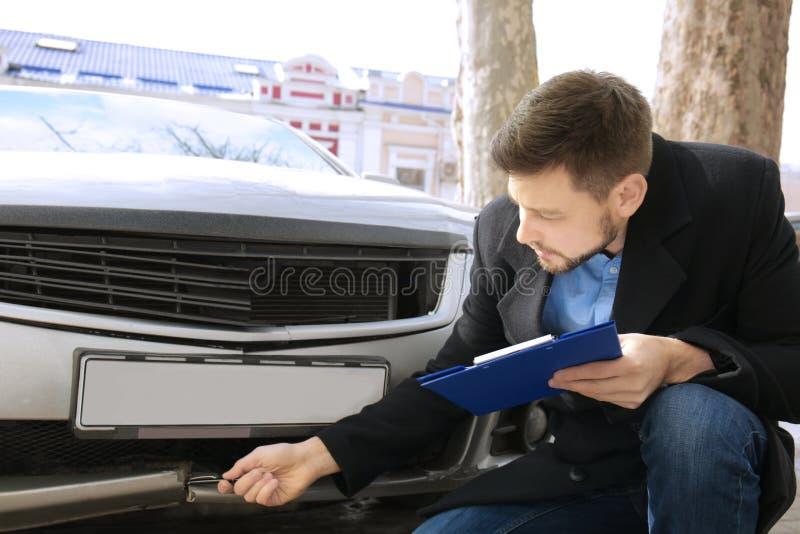 Strata nastawiacz sprawdza samochód po wypadku fotografia royalty free