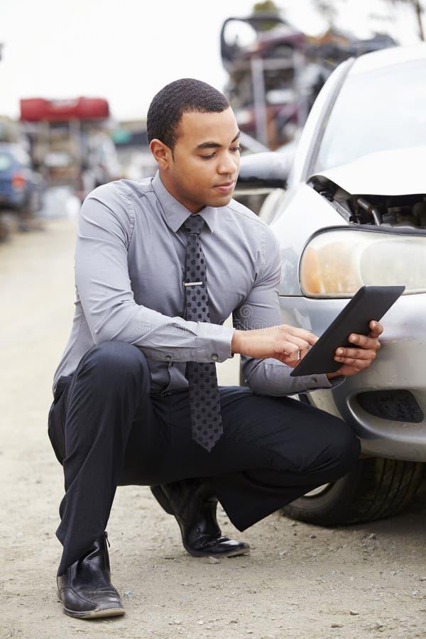 Strata nastawiacz Używa Cyfrowej pastylkę W Samochodowej wrak inspekci obraz stock