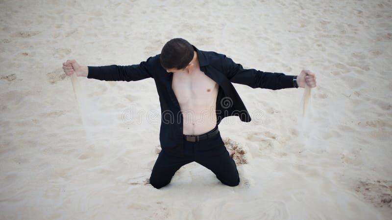 Strata, pojęcie młodego człowieka klęczenie w pustyni Piasek przez palców obrazy royalty free