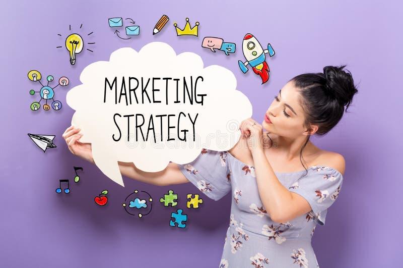 Strategia di marketing con la donna che tiene un fumetto fotografia stock libera da diritti