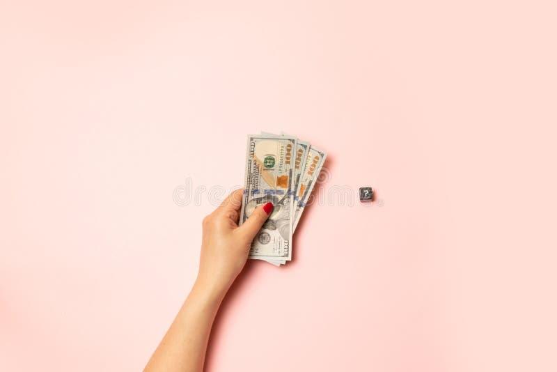 Strategia e concetto di affari Cubo nero con un punto interrogativo Mano femminile con un manicure rosso che tiene le banconote i immagini stock