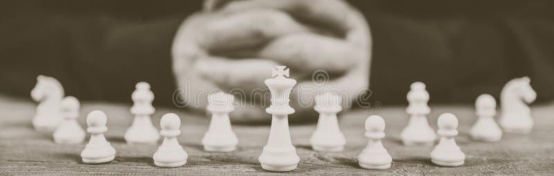 Strategia messa le mani di pianificazione con le figure di scacchi fotografia stock