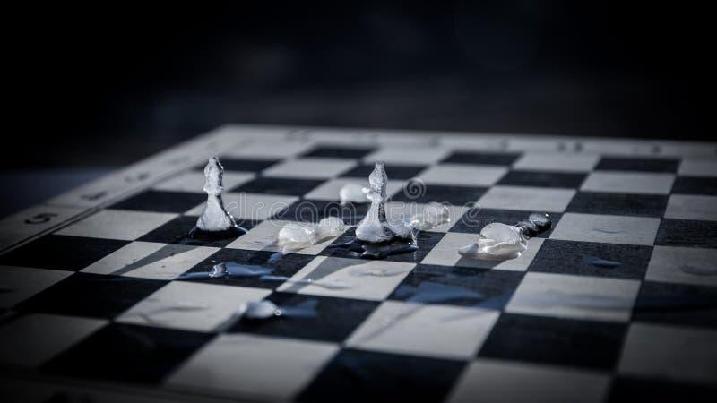 Strategie en tactiekconcept Ijzige berijpte schaakcijfers die zich op een schaakbord tijdens zonsondergang bevinden stock foto's