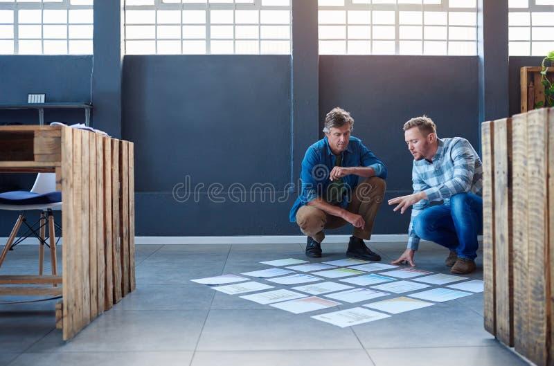 strategizing与在办公室地板上的纸的两个工作同事 库存照片